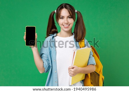 Smiling young woman student in shirt backpack hold notebooks hold mobile cell phone with blank empty screen isolated on green background studio. Education in high school university college concept