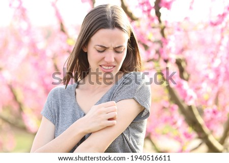 Stressed woman scratching itchy arm after insect bite in a field of peach trees in spring time Royalty-Free Stock Photo #1940516611