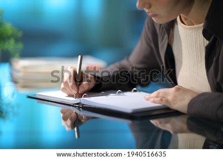 Close up of a woman hands taking notes in a ring binder notebook on a desk in the night at home Royalty-Free Stock Photo #1940516635