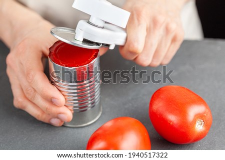 A woman is carefully opening a can of tomato paste on a kitchen counter using a white plastic can opener. She is preparing a meal for which she uses both fresh and pureed preserved tomatoes Royalty-Free Stock Photo #1940517322