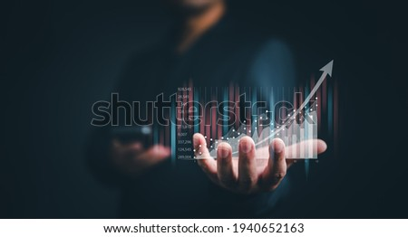 planning and strategy, Stock market, Business growth, progress or success concept. Businessman or trader is showing a growing virtual hologram stock, invest in trading. Royalty-Free Stock Photo #1940652163