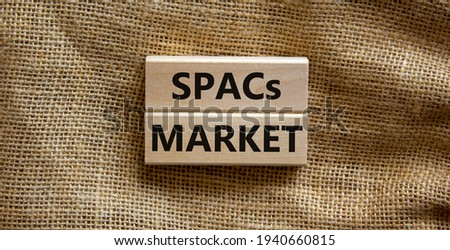 SPACs market symbol. Wooden blocks with words 'SPACs, special purpose acquisition companies market' on beautiful canvas background, copy space. Business and SPACs market concept.