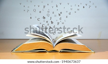 Open book on the wooden table and English alphabet Floating above the book with greyish blue color background.