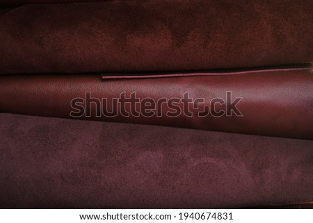 Genuine leather texture.Red burgundy leather and suede in rolls set.Leatherworking. Genuine leather red background.Manufacturing from genuine leather.Hobby and craft  Royalty-Free Stock Photo #1940674831