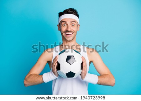 Photo of amazed soccer player catch football wear white singlet isolated over blue color background