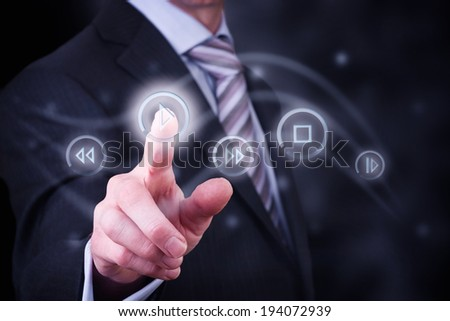 A man pressing a button on a digital screen to control digital media, music and films. #194072939