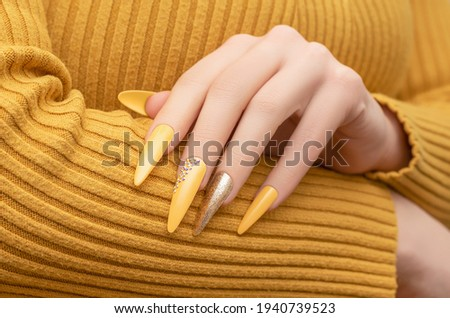 Female hand with yellow nail design. Long nail polish manicure. Woman manicure with gitter gold long nail art Royalty-Free Stock Photo #1940739523