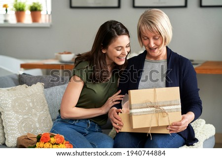 Mother unpacking a gift with her adult daughter                                Royalty-Free Stock Photo #1940744884