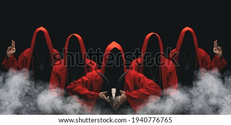 Group of mysterious figures in hooded cloaks in the dark. Leader of sectarians holds skull with horns. Horror scene with smoke. Black background. Royalty-Free Stock Photo #1940776765