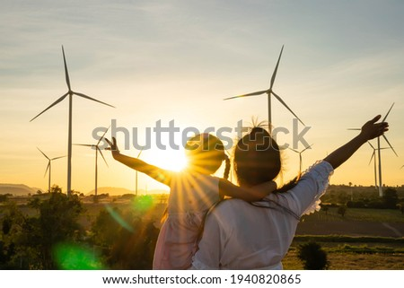 Wind turbines are alternative electricity sources, the concept of sustainable resources, People in the community with wind generators turbines, Renewable energy. Royalty-Free Stock Photo #1940820865