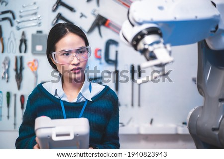 Meeting asian Engineers Maintenance Robot Arm at Lab. they are in a High Tech Research Laboratory with Modern Equipment.Professional Japanese Development Engineer is Testing an Artificial Intelligent. Royalty-Free Stock Photo #1940823943