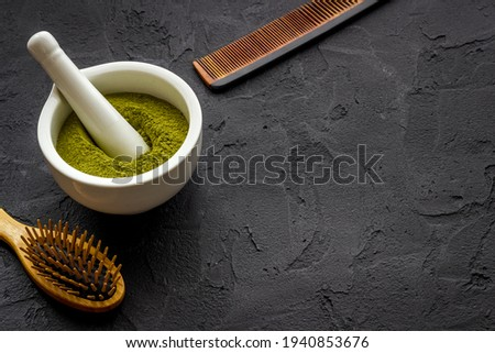 Henna hair dye powder and wooden comb. Henna in wtite mortar