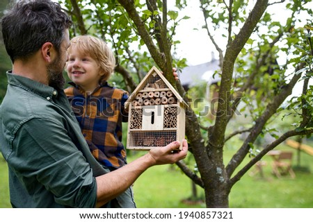 Small boy with father holding bug and insect hotel in garden, sustainable lifestyle. Royalty-Free Stock Photo #1940857321