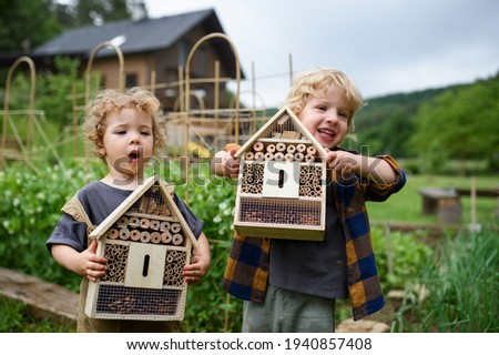 Small boy and girl holding bug and insect hotel in garden, sustainable lifestyle. Royalty-Free Stock Photo #1940857408