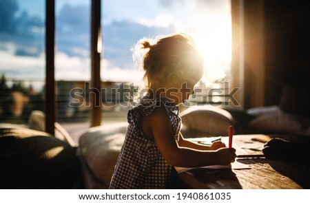 Small girl drawing pictures in wooden cabin, holiday in nature concept.