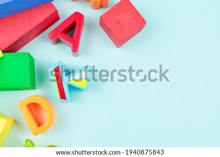 Children's background. Baby toys. Games in the soft constructor, cubes, letters and figures for the sorter. Development of motor skills of the hands and thinking of the child. Space for the text.