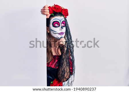Young woman wearing day of the dead custome holding blank empty banner with hand on chin thinking about question, pensive expression. smiling with thoughtful face. doubt concept.