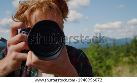 Portrait of male photographer taking photos of mountains during hike. Redhead man looking at pictures on photo camera outdoor. Smiling hiker shooting green landscape with professional camera