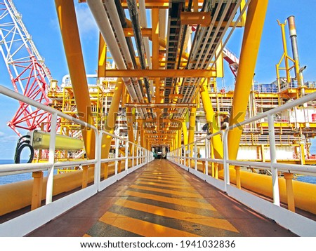 walkway between oil and gas processing platform offshore and flare tip                                Royalty-Free Stock Photo #1941032836