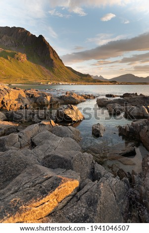 Long exposure water in the beach with sunset and cloud at Haukland Beach Lofoten Islands,  Leknes. pictures stones unfocus view on the arctic beach of Lofoten islands, pictures stones on the arctic