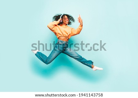 Beautiful black woman with afro curls hairstyle.Smiling model orange hoodie.Sexy carefree female listening music in wireless headphones. Jumping in studio on blue background.Dynamic movement