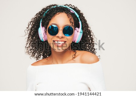 Beautiful black woman with afro curls hairstyle.Smiling model in sweater and jeans.Sexy carefree female listening music in wireless headphones.Posing in studio on white background in sunglasses