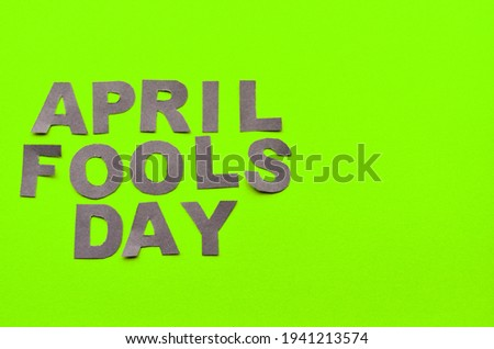 Image caption April Fools' Day made of grey letters on a green background with a copy space. High quality photo