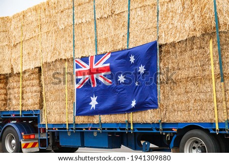 Truck filled with hay bales being transported to Aussie farmers in drought with Australian flag attached to the side Royalty-Free Stock Photo #1941309880