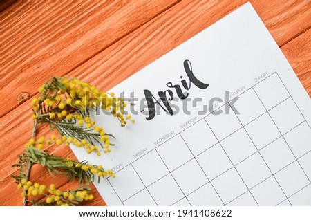 Simple desk calendar for April 2021 with spring flowers. Place for text. Deadline concept with sheet of monthly calendar.  Royalty-Free Stock Photo #1941408622