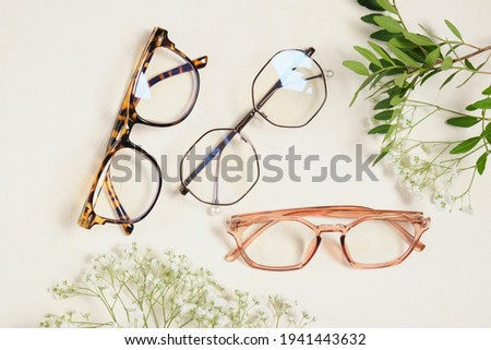 several trendy stylish glasses and flowers on a beige background place copy top view, optics, shop of glasses and frames concept Royalty-Free Stock Photo #1941443632