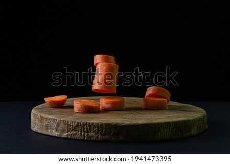 Carrots on a dark background. Sliced carrots fall on a wooden board on a black background. Healthy food