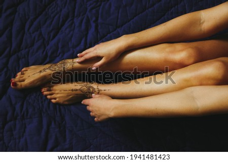 Close-up of female legs and hands with henna tattoo on the feet on a blue background. Gently feminine graceful decoration, respect for a woman, love and take care of yourself.