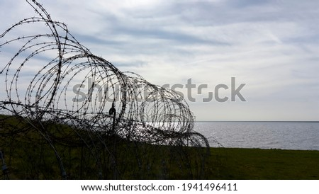 Closeup of old metal barbed wire from the second world war. Sharp razor wire fence near the sea during sunset.  Concept of prison, immigration, detention, boundary, defence or war. Royalty-Free Stock Photo #1941496411