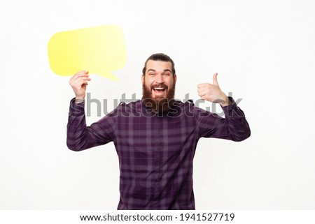 Photo of amazed smiling bearded man showing thumb up and holding yellow speech bubble.