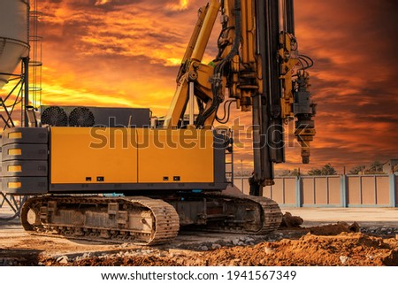 Hydraulic drilling rig against the backdrop of the sunset sky. Installation of bored piles by drilling. Foundations and foundations. Drilling in the ground Royalty-Free Stock Photo #1941567349