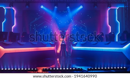 eSports Winner Trophy Standing on a Stage in the Middle of the Computer Video Games Championship Arena. Two Rows of PC for Competing Teams. Stylish Neon Lights with Cool Area Design. Royalty-Free Stock Photo #1941640990