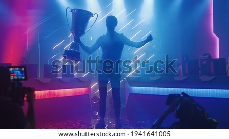 Professional Video Games Player Tournament Winner Celebrates Victory Cheering and Holding Trophy. Big Stylish Neon Bright Championship Arena doing Pro Computer Gaming Event with Online Streaming Royalty-Free Stock Photo #1941641005