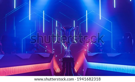 eSports Winner Trophy Standing on a Stage in the Middle of the Computer Video Games Championship Arena. Two Rows of PC for Competing Teams. Stylish Neon Lights with Cool Design. Royalty-Free Stock Photo #1941682318