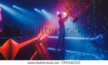 eSports Winner Trophy Standing on a Stage in the Middle of the Computer Video Games Championship Arena. Two Rows of PC for Competing Teams. Stylish Neon Lights with Cool Area Design. Royalty-Free Stock Photo #1941682321