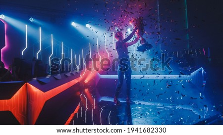 eSports Winner Trophy Standing on a Stage in the Middle of the Computer Video Games Championship Arena. Two Rows of PC for Competing Teams. Stylish Neon Lights with Cool Area Design. Royalty-Free Stock Photo #1941682330