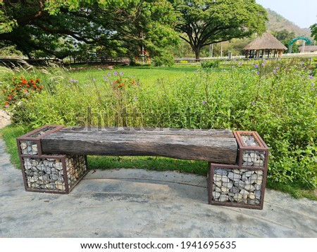 A park bench made of large planks There is a grate to put the stones supporting both ends.  Royalty-Free Stock Photo #1941695635
