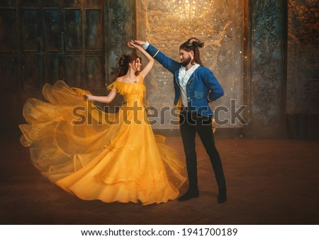 loving couple is dancing at fairy ball. Happy beauty woman fantasy princess in yellow dress and guy is enchanted beast, horns on head Girl whirls in arms of male prince. Man monster carnival costume.