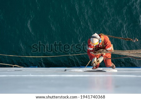 Seaman ship crew working aloft at height derusting and getting vessel ready for painting. Boat maintenance. Royalty-Free Stock Photo #1941740368