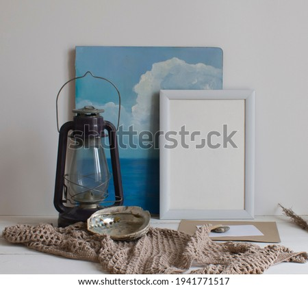 Still life in the marine style. A kerosene lamp, a shell, stones, an empty form, an empty picture in a frame, a picture on a marine theme, a knitted tablecloth on a white table on a light background.