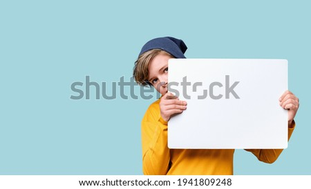 Young teen caucasian boy peeking out from behind white notice board with copy space. Blue background banner.