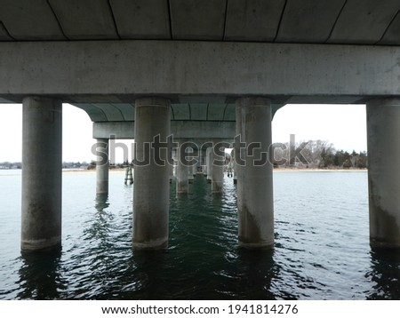 Pillars under the bridge looking over the water in Sag Harbor, New York Royalty-Free Stock Photo #1941814276