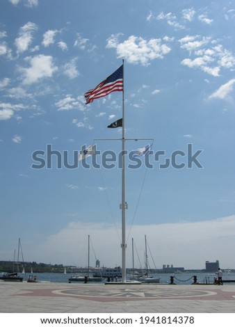 Boston Harbor with American flag and Massachusetts flag on display on the flagpole Royalty-Free Stock Photo #1941814378