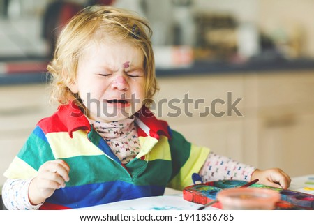 Sad crying baby girl learning painting with water colors. Little toddler child drawing at home, using colorful brushes. Angry child in hysteric crisis.