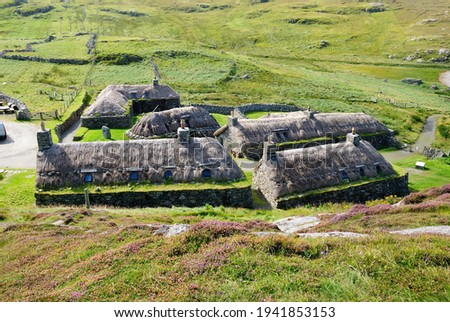 Traditional blackhouses roofed with wooden rafters covered with a thatch of turf with cereal straw (or reed) in Garenin township on the Isle of Lewis in the Outer Hebrides of Scotland, UK Royalty-Free Stock Photo #1941853153