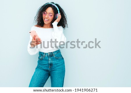 Beautiful black woman with afro curls hairstyle.Smiling model in sweater and jeans.Sexy carefree female listening music in wireless headphones.Posing in studio near light blue wall. Holds smartphone